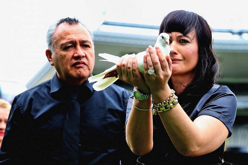 Widow of New Zealand All Blacks rugby legend Jonah Lomu, Nadene Lomu (right) releases a dove at Eden Park.