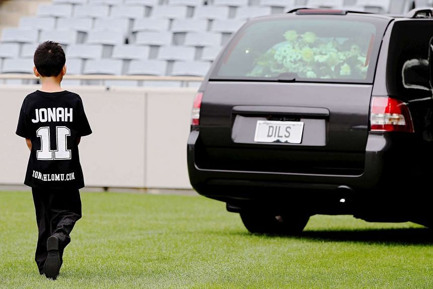 The son of former All Black player Jonah Lomu, Dhyreille Lomu, walks behind the hearse containing his father's casket as it leaves a memorial service at Eden Park.