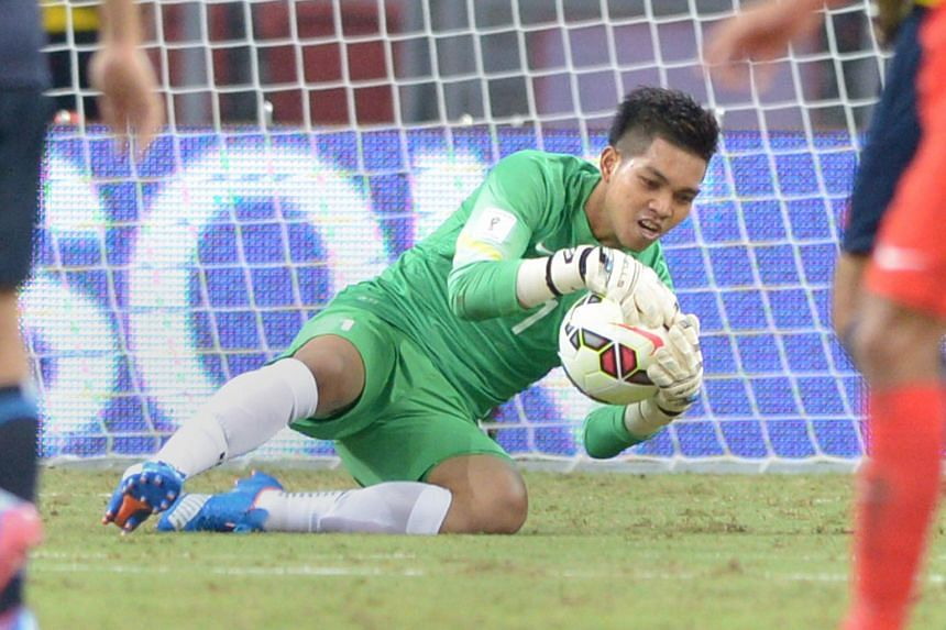 Singapore goalkeeper Izwan Mahbud saving a shot during the match between Singapore and Japan in the Group E World Cup Qualifier.
