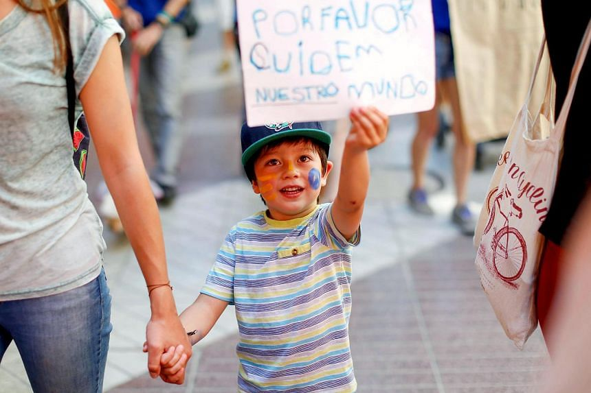 "A child holds up a banner that reads ""Please, take care of our world"" during a rally held the day before the start of the Paris Climate Change Conference in Santiago, Chile. on Nov 29, 2015."