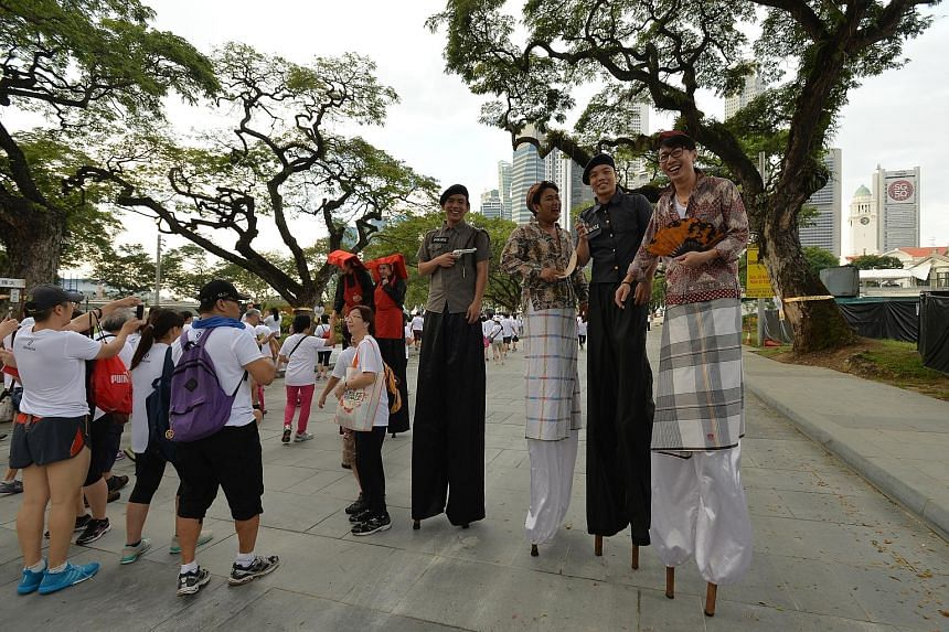 Stiltwalkers (above, right) entertaining the crowds, while a participant (right) visits the SG Heart Map Festival after the walk. The Jubilee Bridge (below) was one of the landmarks along the route. Participants crossing the Helix Bridge at the SG50