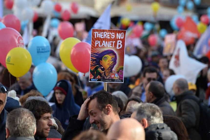 """A demonstrator holds a placard that reads """"There is No Planet B"""" at Piazza Campo de Fiori in Rome during a rally calling for action on climate change on Nov 29, 2015."""