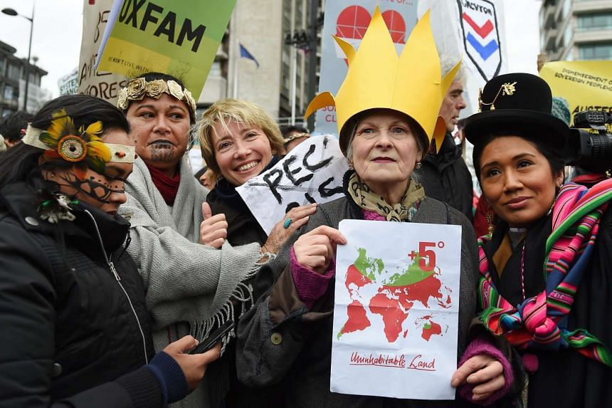 British actress Emma Thompson (3rd from left) and British fashion designer Vivienne Westwood (2nd from right) with indigenous women from South America during a climate change march in London on Nov 29, 2015.