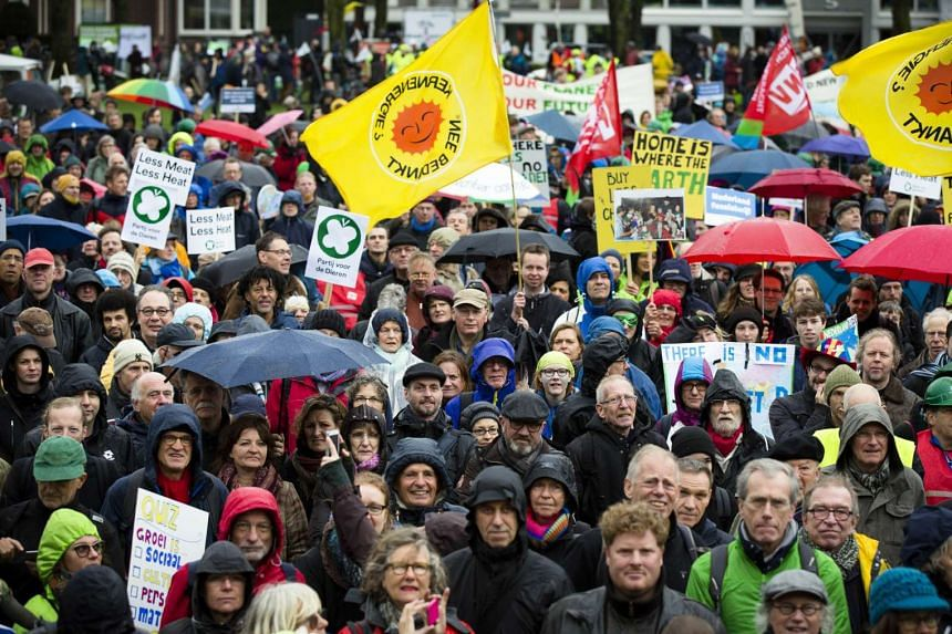People hold flags and placards at a climate change march in Amsterdam on Nov 29, 2015.