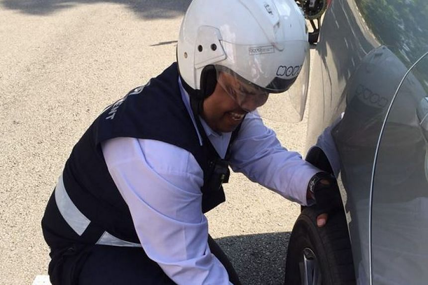 LTA enforcement officer Kharul Nizam changing the flat tyre on Mr Kevin Tan's car.