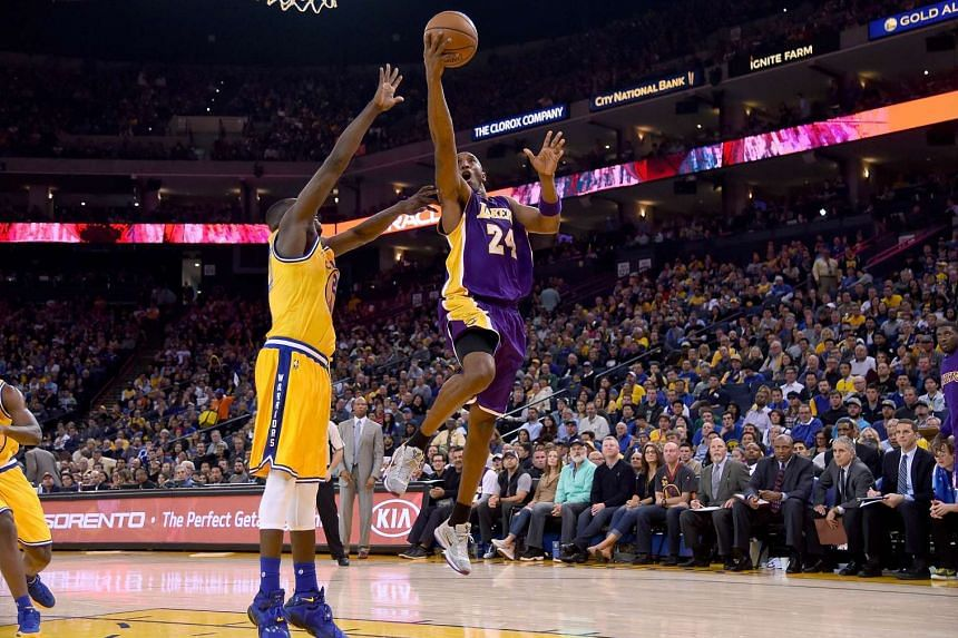 Kobe Bryant #24 of the Los Angeles Lakers goes up for a layup over Draymond Green #23 of the Golden State Warriors.