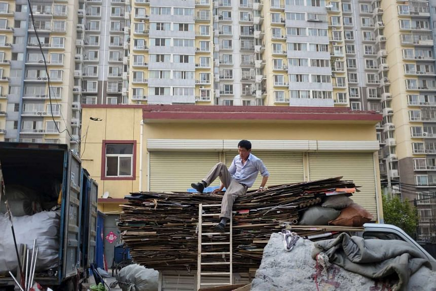 A rag-and-bone man tries to come down from a truck in front of an apartment block, in Beijing, China.