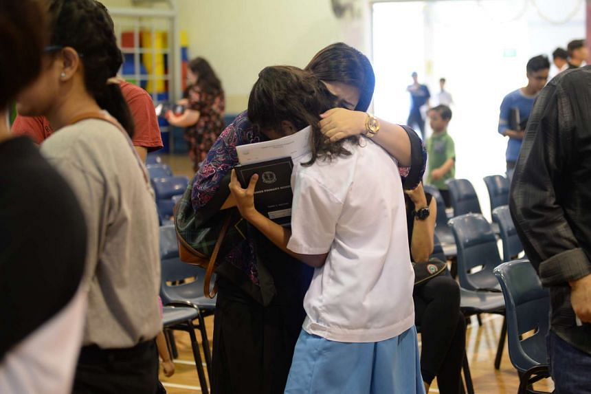 A parent hugging her daughter after the release of the 2015 PSLE results at Eunos Primary School.