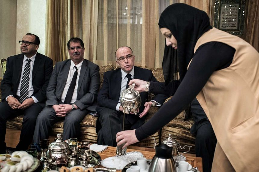 A woman pours French Interior Minister Bernard Cazeneuve  tea at the Grand Mosque in Lyon last month.