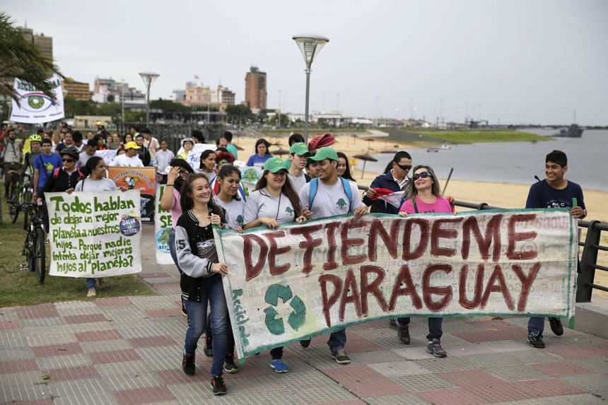 """Protesters hold a banner that reads """"Defend Paraguay"""" at a climate change march  in Asuncion on Sunday."""