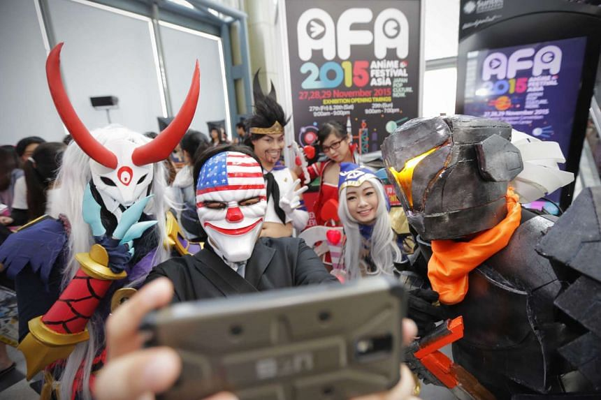 Cosplayers (above) taking a selfie. Mr James Ng, a contestant at the regional cosplay competition, spent $500 making his costume for Saint Seiya, and student Eileen Chee dressed as Ashe from online game League Of Legends.