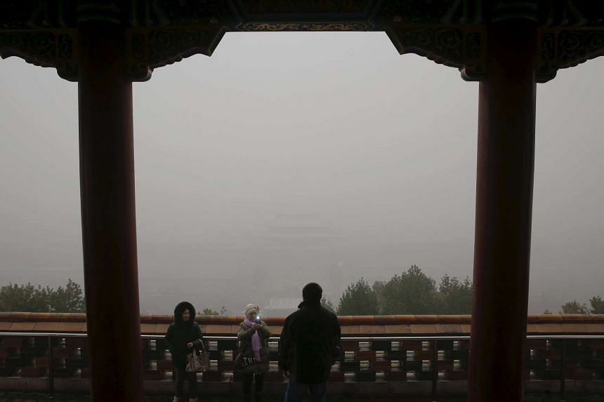 The Forbidden city is barely seen as visitors take pictures on an extremely polluted day in Beijing on Dec 1, 2015.