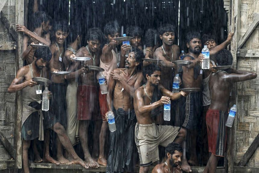 Migrants, who were found at sea on a boat, collect rainwater at a refugee camp in Myanmar.