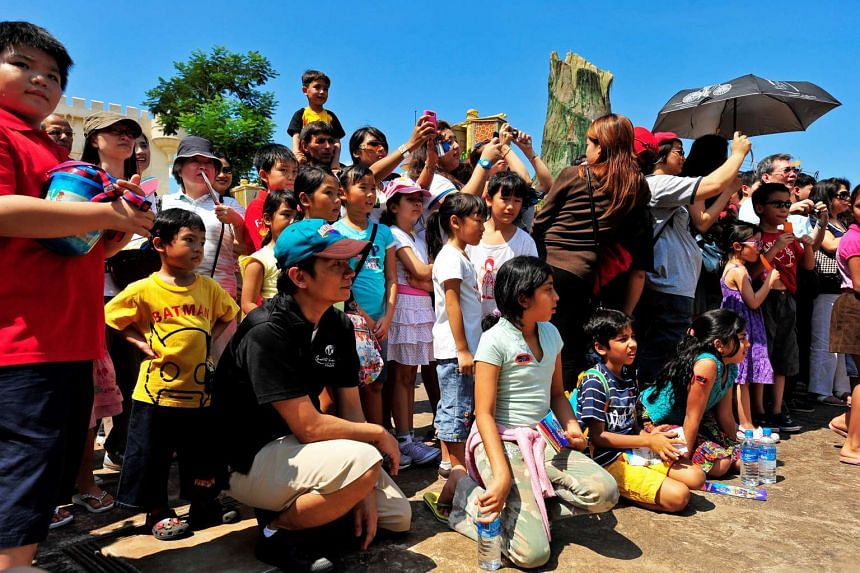 In a black polo and brown shorts, about 60 character escorts like John Lui (third from left) keep fragile fantasy characters such as Po, the Kung Fu Panda and Princess Fiona from being pushed, prodded or punched.