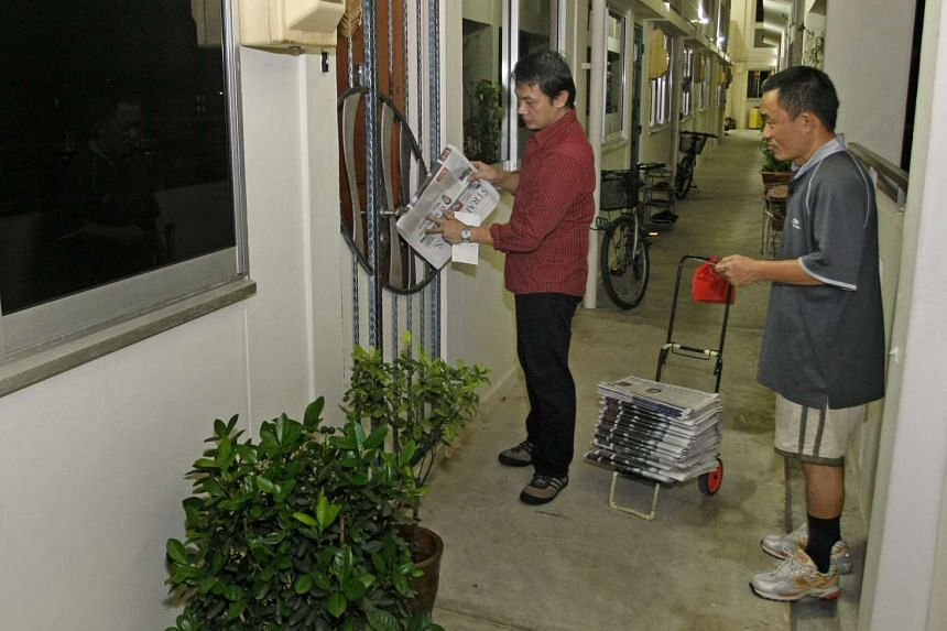 Newspaper deliveryman Richard Lim (right) shows reporter John Lui how to deliver The Straits Times at lightning speed.