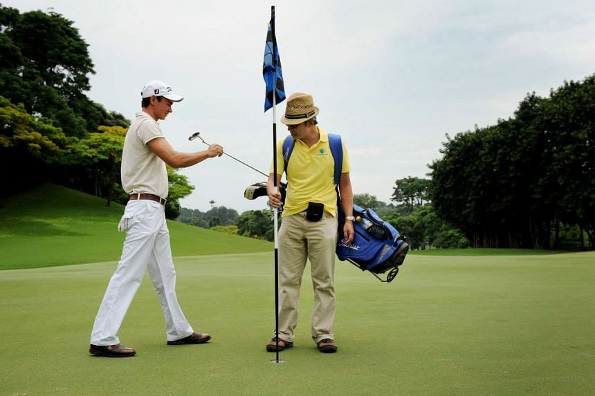 Among a caddie's tasks is removing the flag before his golfer putts.