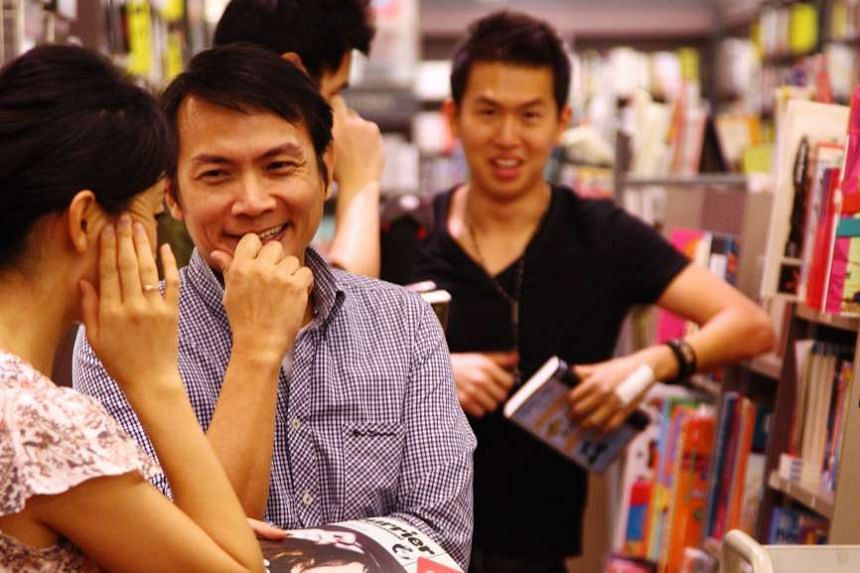 John Lui (centre) tries to chat up the first woman at a book store with help through hand signals from dating coach Xavier See (right).