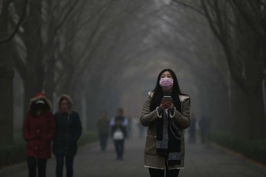 A woman wearing a mask walk in a street in a Yonghegong Lama temple compound seen shrouded in smog in Beijing, China, on Nov 30, 2015. Beijing issued an orange alert for heavy smog on Nov 30, the highest level this year.