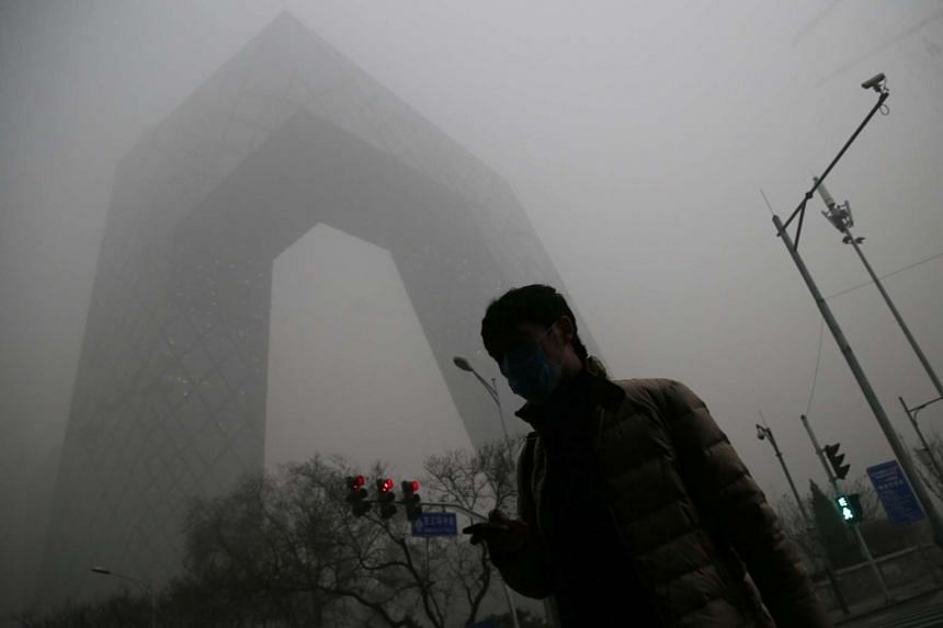 A man wears a mask in front of the China Central Television (CCTV) Tower during a hazy day in Beijing city, China.