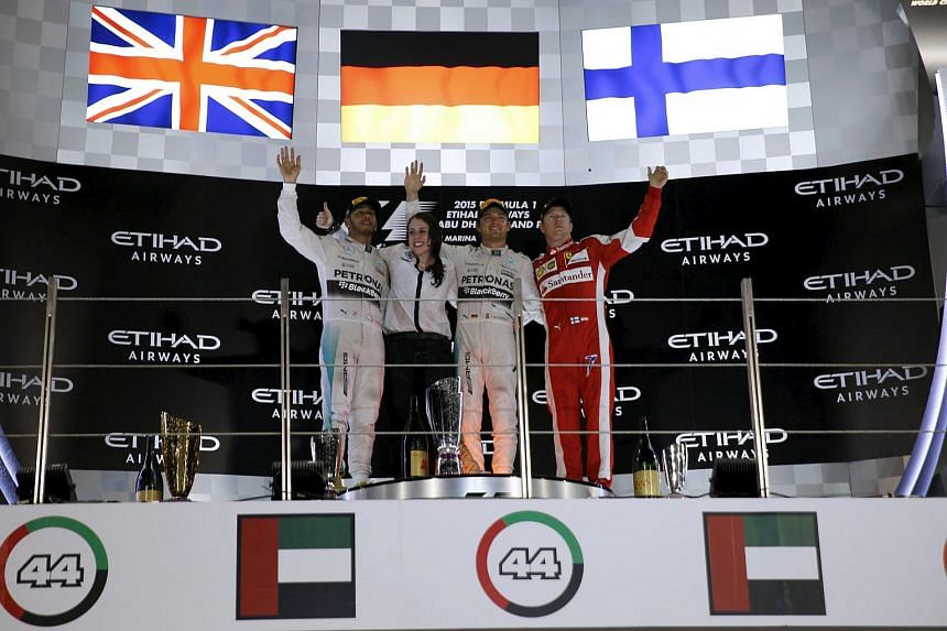 (From left) Lewis Hamilton, Nico Rosberg and Kimi Raikkonen pose with a Mercedes team member at the podium of the Abu Dhabi F1 Grand Prix at the Yas Marina circuit in Abu Dhabi Nov  29, 2015.