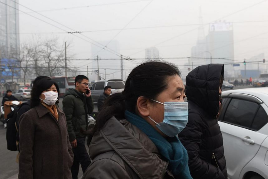 Pedestrians wear masks on a polluted day in Beijing.