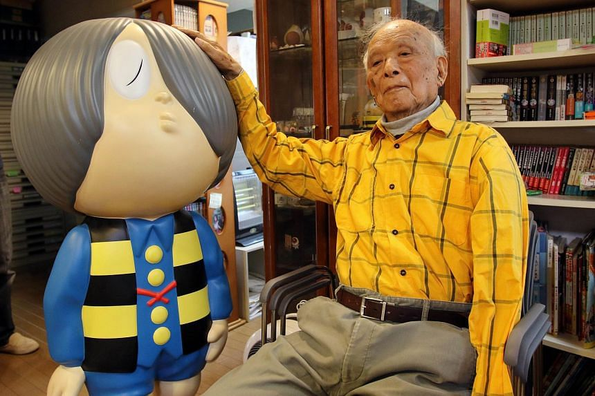 Japanese cartoonist Shigeru Mizuki sitting next to his character Kitaro during an interview on May 12, 2015.