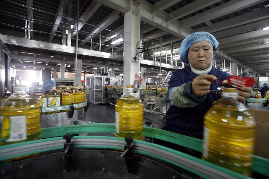 A worker checking items on a production line at a cooking oil factory in Wuhan on Nov 3.