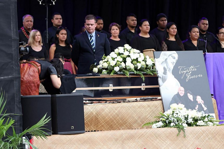 The widow of late New Zealand All Blacks rugby legend Jonah Lomu, Nadene Lomu (left) laying a shirt on her husband's casket during the memorial service.