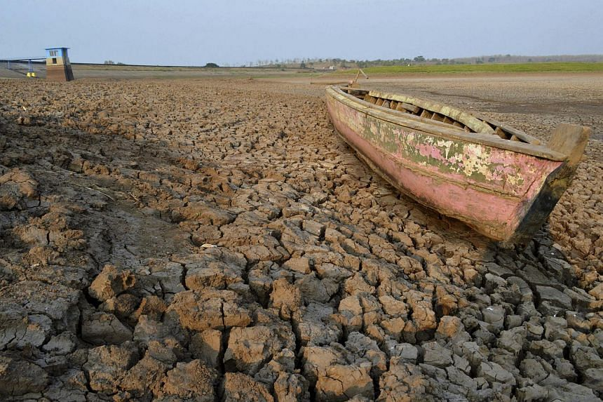 A wooden boat is seen stranded on the dry cracked riverbed of the Dawuhan Dam during drought season in Indonesia.