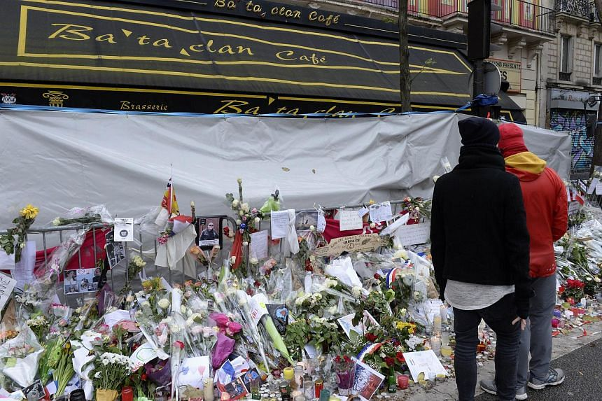 People stop to look at the memorial set-up in front of the Bataclan Concert Hall on Nov 29, 2015 in Paris.
