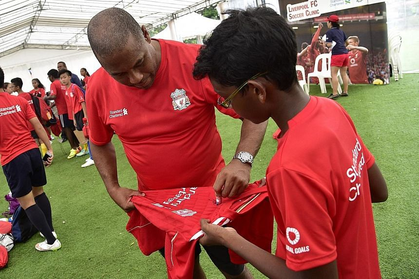 Former Liverpool star John Barnes signing an autograph. He is in town to help conduct a football clinic for youngsters.