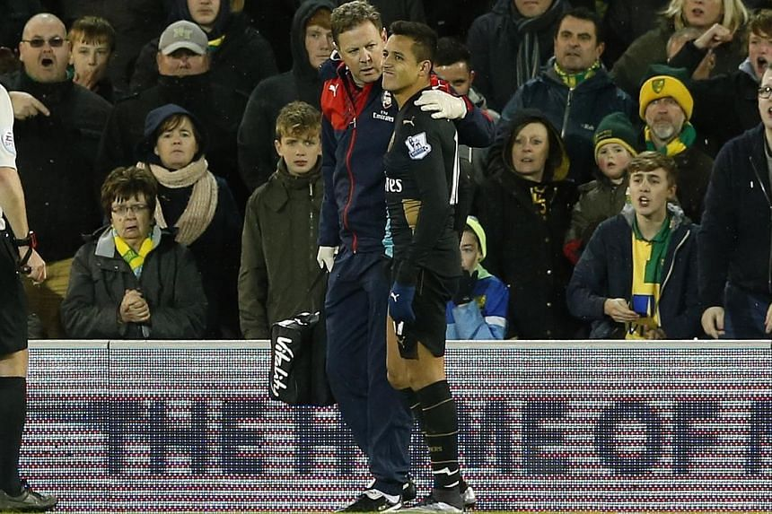 Arsenal's Chilean forward Alexis Sanchez going off injured in the 1-1 draw against Norwich on Sunday. Laurent Koscielny and Santi Cazorla also hurt their hip and knee respectively.