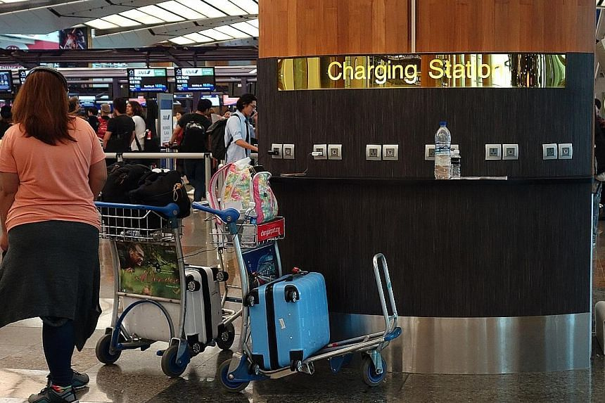 A cellphone charging station at Changi Airport Terminal 2 departure hall. The airport has installed 880 mobile phone charging stations, 23 hot water dispensers and water coolers in its gate hold rooms at the request of travellers.