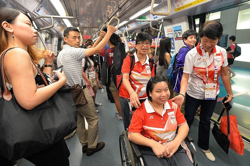 Boccia player Koh Kai Hui (in wheelchair) making her way on the Circle Line from Stadium MRT station to the Games Village at Marina Bay Sands together with Dr Teo-Koh Sock Miang (right), SNPC president, and other officials and athletes.