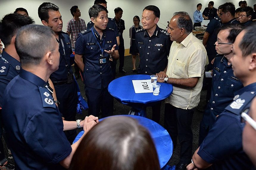 Home Affairs Minister K. Shanmugam chatting with police officers at the tea reception at Police Cantonment Complex yesterday. With him are Commander of Ang Mo Kio Division Lian Ghim Hua (2nd from right), Commissioner of Police Hoong Wee Teck (4th fro