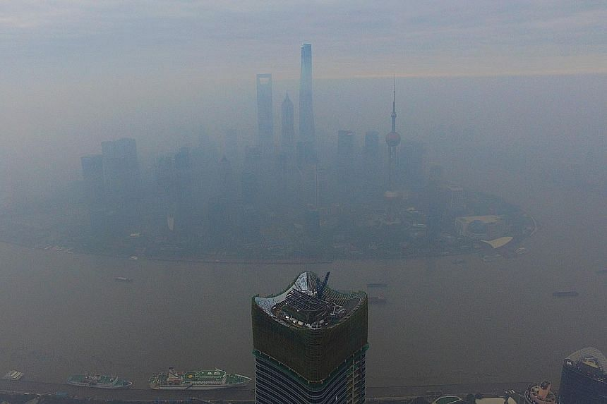 The Shanghai Pudong Lujiazui area shrouded in thick smog yesterday. In Beijing, the high smog level triggered an orange-level pollution alert over the weekend, with residents advised to stay indoors and some factories ordered shut.