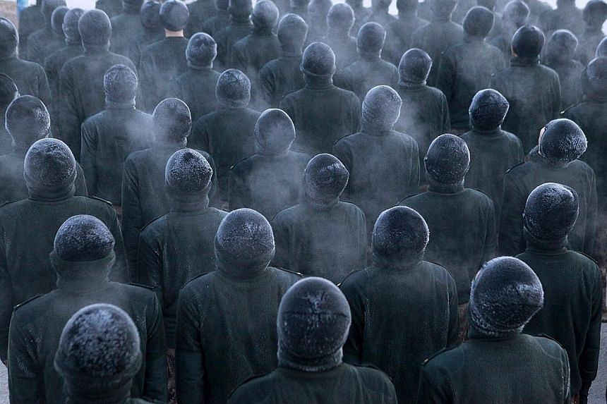 New recruits in the People's Liberation Army standing in formation during a training session in frigid winter conditions at a military base in Heihe, Heilongjiang province, China, on Sunday. Local temperatures reached minus 20 deg C that day.