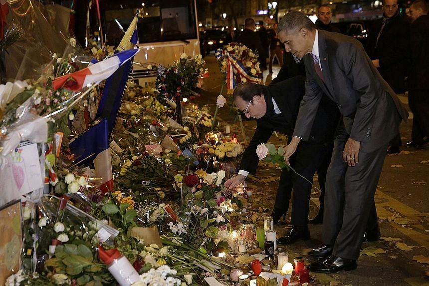 US President Barack Obama paying a silent tribute yesterday to those who died in Paris' Bataclan concert hall on Nov 13. With him was French President Francois Hollande. Mr Obama is in Paris for the United Nations climate change summit. Attending the