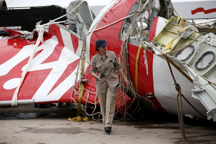 An Airbus investigator walks near part of the tail of the AirAsia QZ8501 plane in Kumai Port on Jan 12, 2015.