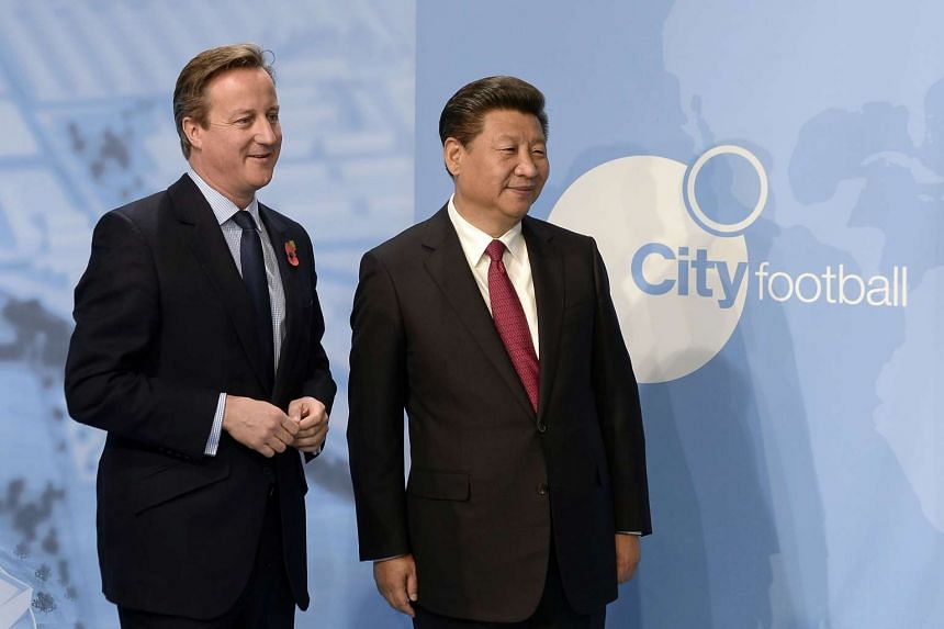 A file picture of British Prime Minister David Cameron (L) and Chinese President Xi Jinping during a visit to the City Football Academy in Manchester. Chinese investors China Media Capital (CMC) and CITIC Capital have bought a 13 per cent stake in th