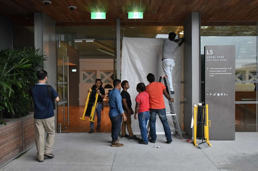 Workers putting up screening and barricades at the shattered glass door at National Gallery Singapore.