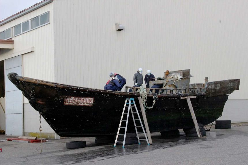 Officials investigating a wooden boat at the Fukui port in Sakai city, western Japan on Nov 24, 2015, after it was found drifting off the coast of Fukui.