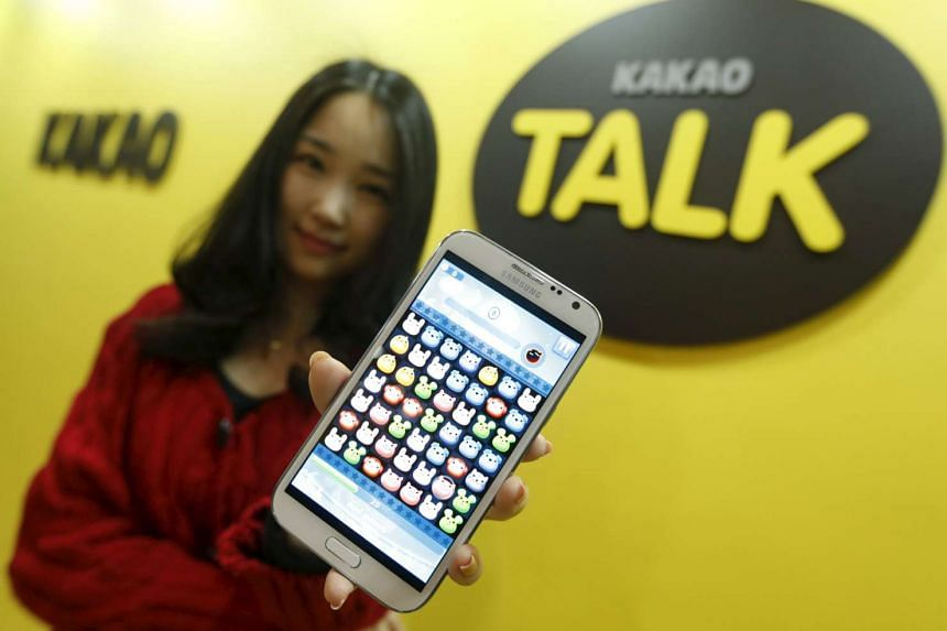 An employee of mobile messager Kakao Talk displays the mobile game Anipang on a smartphone.