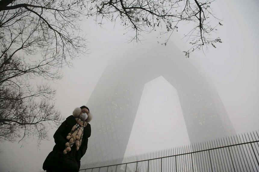 A woman wearing a protective mask walks in front of the China Central Television building on an extremely polluted morning in Beijing.