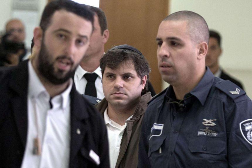Yosef Haim Ben-David (centre) is escorted by Israeli policemen in Jerusalem on Monday.