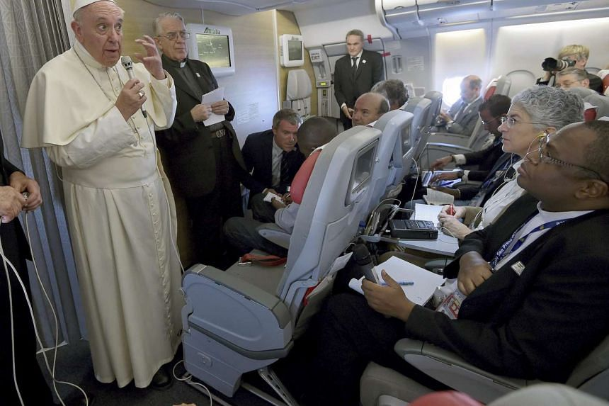 Pope Francis gestures to the media on board the papal plane en route to Rome on Monday.