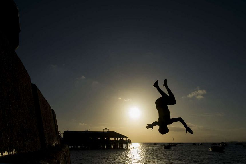 A youth jumps into the Indian Ocean at the historical Stone Town of Zanzibar on Nov 2.
