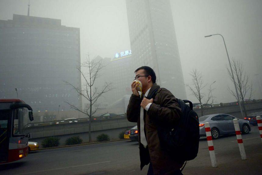 A man wearing a mask walks along a road in heavy pollution in Beijing on Dec 1, 2015.