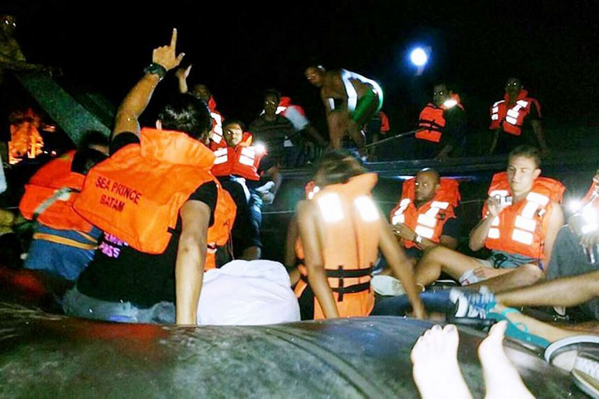 Passengers climbing on board life rafts after the ferry hit a floating object.