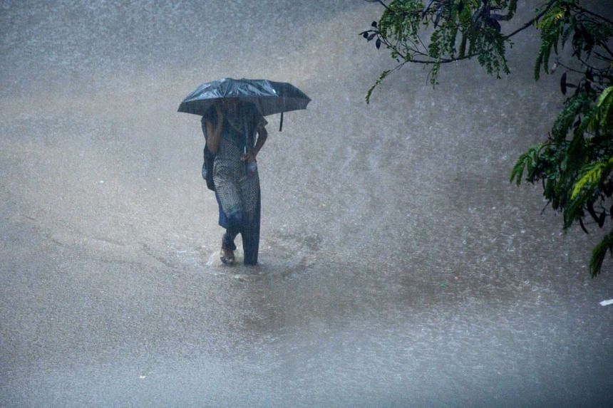 A young Indian woman walks under an umbrella through floodwaters in Chennai.